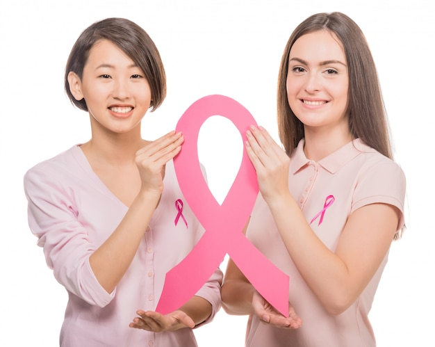 Happy women wearing pink tops and ribbons for breast cancer.