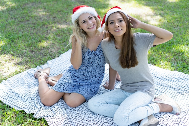 Happy women wearing santa hats and posing on grass in park