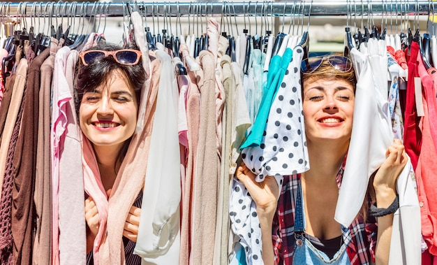 Happy women at weekly flea market - female friends having fun together shopping cloth on sunny day