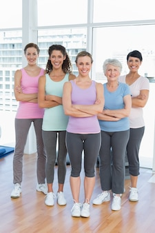 Happy women with arms crossed in yoga class