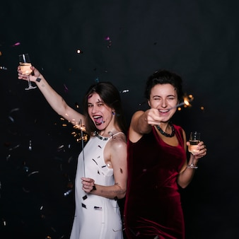 Happy women with champagne glasses and sparklers