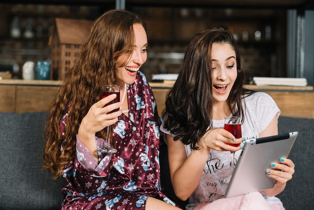 Happy women with drinks using digital tablet