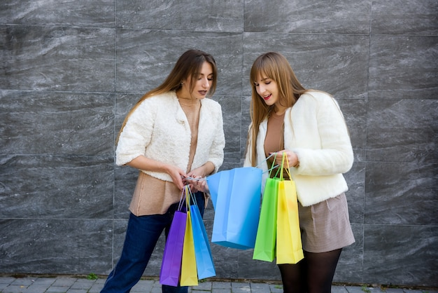 Happy women with shopping bags in fur coats posing on city street