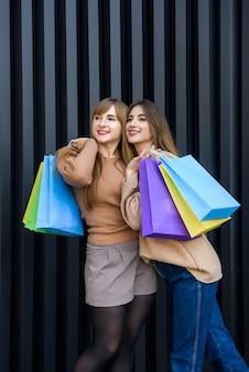 街の通りでポーズをとって毛皮のコートで買い物袋を持つ幸せな女性