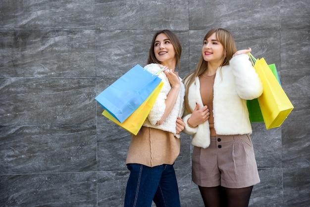 도시 거리에 포즈를 취하는 모피 코트에 쇼핑백과 함께 행복한 여자