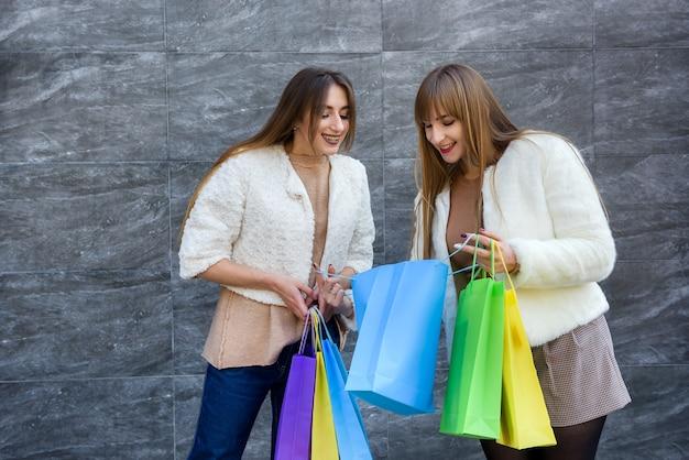Счастливые женщины с сумками в шубах позируют на улице города