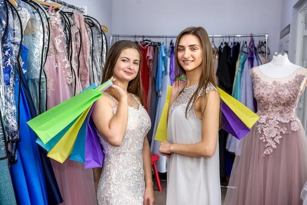 Счастливые женщины с хозяйственными сумками в магазине одежды