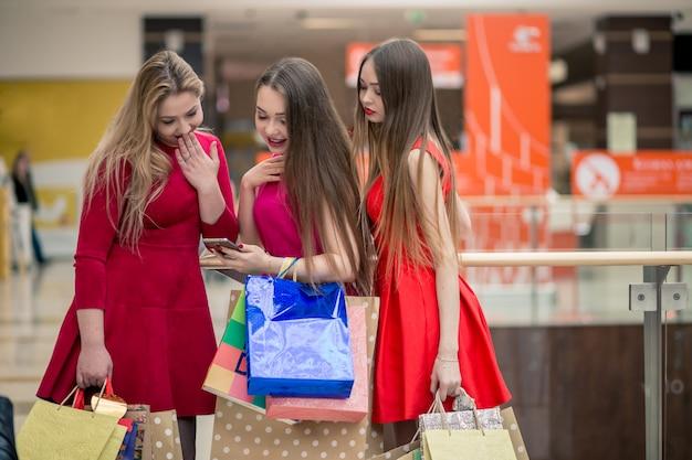 スマートフォンと買い物袋を持つ幸せな女性
