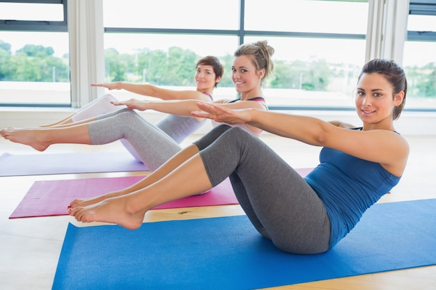 Happy women in yoga class doing boat pose