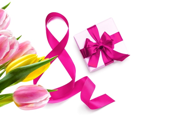 Счастливый женский день. декоративный розовый бант с подарочной коробкой и тюльпанами на белом фоне. международный женский день 8 марта дизайн.