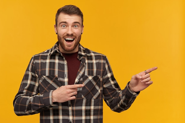 Happy wondered young man in plaid shirt with beard and opened mouth looks amazed and pointing away at empty space by two fingers over yellow wall