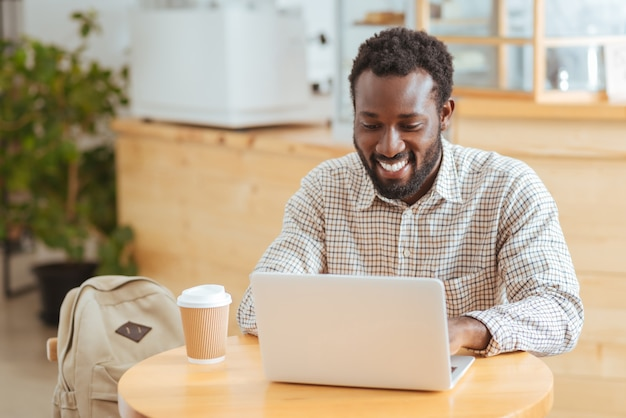 Счастливый рабочий. очаровательный молодой человек сидит за столом в кафе и работает на ноутбуке, улыбаясь