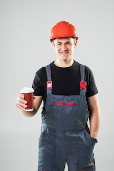 Happy worker in hard hat holding paper cup with coffee to go and smiling at camera