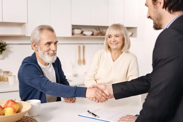 Счастливого рабочего времени. очаровательный опытный квалифицированный брокер встречается с пожилой парой клиентов во время работы и обменивается рукопожатием
