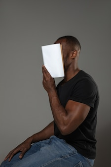 Happy world book and copyright day, read to become someone else - man covering face with book while reading on grey wall.