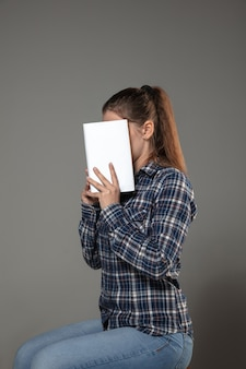 Happy world book and copyright day, read to become someone else - woman covering face with book while reading on grey wall.