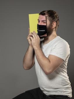 Счастливого всемирного дня книги 2020 года, будьте осторожны и читайте, чтобы стать кем-то другим - человеком, закрывающим лицо книгой в маске во время чтения на сером студийном фоне. празднование, образование, искусство, концепция защиты.