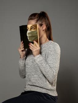 幸せな世界の本の日2020、安全で他の誰かになるために読んでください-灰色のスタジオの背景で読んでいる間、マスクの本で顔を覆っている女性。祝う、教育、芸術、保護の概念。