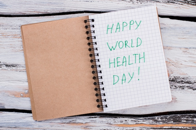 Happy world health day concept. opened notepad with wishes. white wooden table.