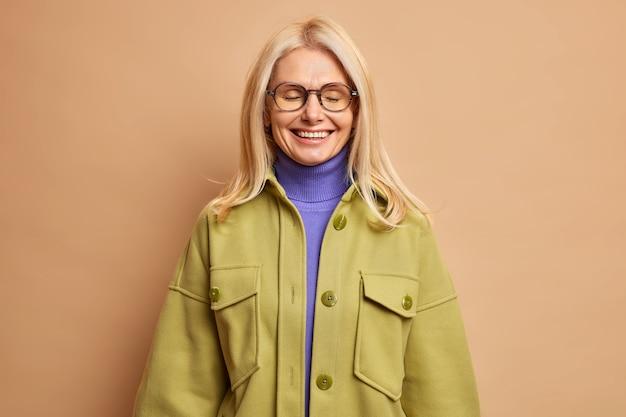 幸せなしわのある金髪の女性が目を閉じて笑顔が優しく何か楽しいものがポジティブな感情を表現していることを思い出します。