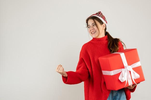 白の上に立っている勝利のジェスチャーを示す彼女の贈り物を保持しているサンタの帽子を持つ幸せなクリスマスの女の子
