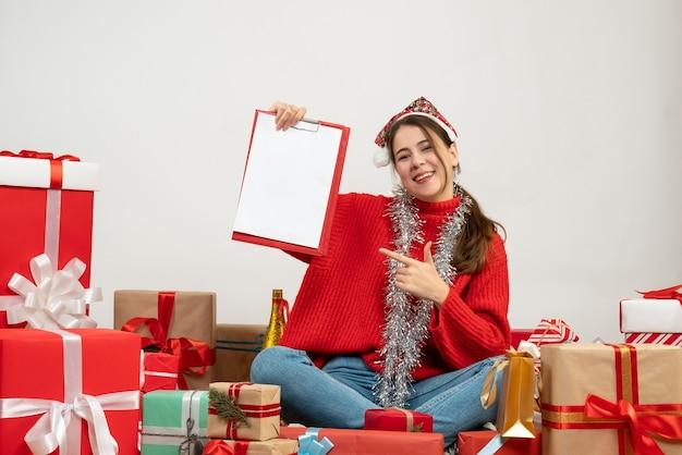 흰색 선물 주위에 앉아 서류를 들고 산타 모자와 함께 행복 한 크리스마스 소녀