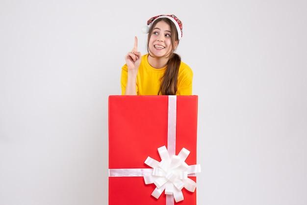 화이트에 큰 크리스마스 선물 뒤에 서있는 산타 모자와 함께 행복 한 크리스마스 소녀