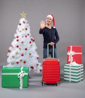 彼のスーツケースを保持しているサンタの帽子を持つ幸せなクリスマスの男