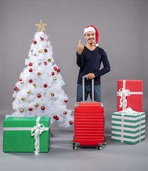 クリスマスツリーとギフトボックスの近くにサンタの帽子をかぶった幸せなクリスマスの男