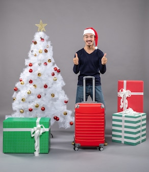 Счастливый рождественский мужчина в шляпе санта-клауса показывает вверх знак