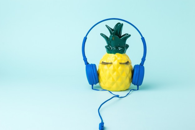 A happy yellow pineapple in blue headphones on a blue background. the love of music.