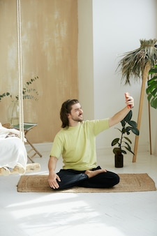 Happy yoga teacher on video call via phone, handsome man sitting in lotus pose and using smartphone, mindfulness concept