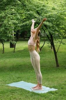 夏に公園で運動する幸せなヨギの女の子