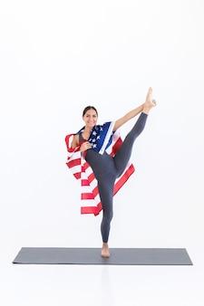 흰색 바탕에 미국 국기와 함께 요가 운동을 하는 행복한 요기 여성