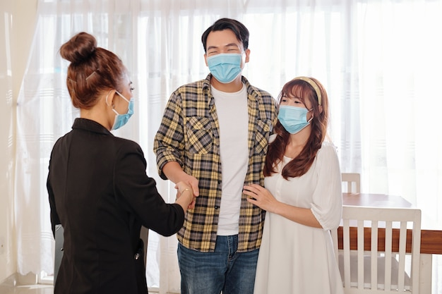 Happy youg asian couple in medical masks meeting with real estate agent in new house