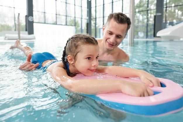 Счастливый молодой активный мужчина учит свою маленькую дочь плавать во время совместного отдыха в современном спа-центре или на летнем курорте