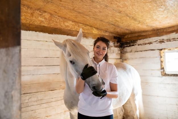 Счастливая молодая активная женщина в белой рубашке и черных кожаных перчатках обнимает морду породистой кобылы в конюшне