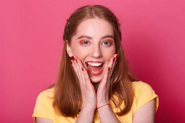 Счастливая молодая очаровательная женщина с триумфом что-то кричит, имеет прекрасные новости, хочет поделиться своим счастьем