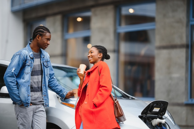 Happy young adult african american man and smiling woman charging electric car.