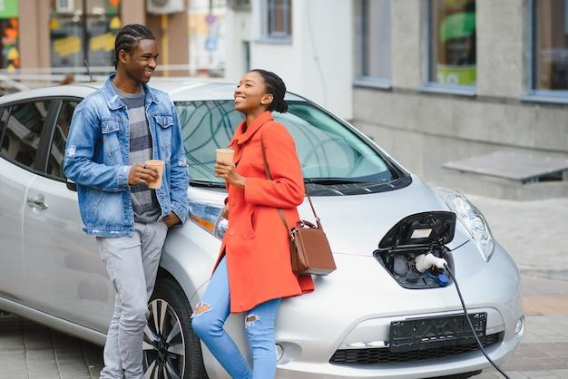 행복 한 젊은 성인 미국 남자와 웃는 여자 전기 자동차를 충전.