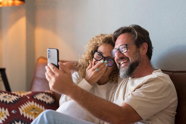 幸せな若い大人のカップルが電話でビデオ通話をする-陽気な人々がソファに座って自宅から携帯電話でオンラインで友達を話したり聞いたりする-休日のリモートお祝いのコンセプト