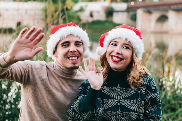 Happy young adult couple waving at camera on video call via laptop on christmas day. wallpaper for video call.