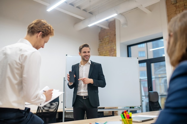 Счастливый молодой взрослый человек в темном костюме и белой рубашке, указывая на смартфон в руке и коллег в офисе