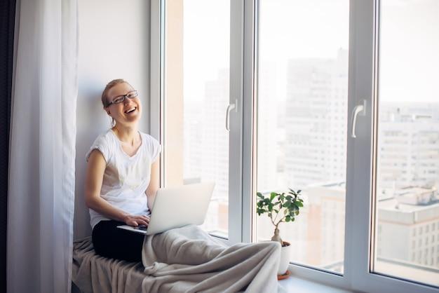 Счастливый молодой взрослая женщина фрилансер в очках, сидя на фоне окна. смеющаяся блондинка работает на ноутбуке. рабочее место на подоконнике. концепция домашнего офиса.
