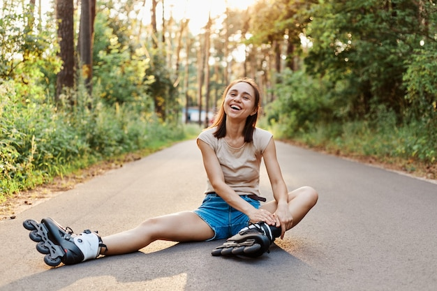 Rollerblades에서 행복 한 젊은 성인 여자, 도로에 앉아 베이지 색 t 셔츠와 짧은 청바지를 입고 카메라를 직접보고 행복 하 게 웃 고, 여성 rollerskating.