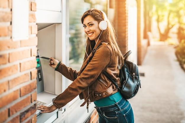 헤드폰을 끼고 현금 지급기 앞에 서서 신용카드나 직불카드를 들고 웃고 있는 행복한 젊은 성인 여성.