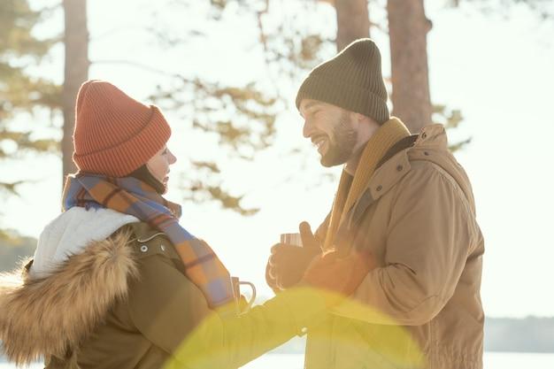 お互いの前に立って、話し、冬の週末を楽しんでいる間、熱いお茶を飲んで暖かい冬のウェアで幸せな若い愛情のこもったカップル