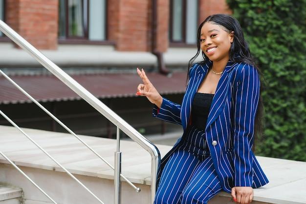 Счастливый молодой афро-американский бизнесмен в городе