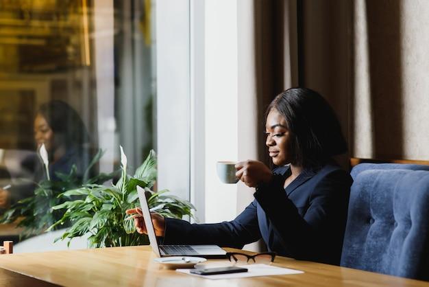 Счастливый молодой афро-американский бизнесмен с помощью компьютера