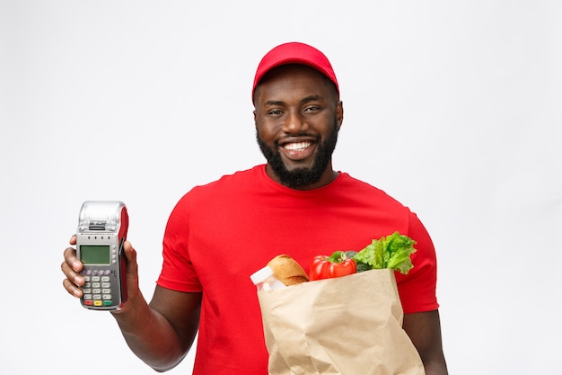 Happy young african american delivery man holding up an electronic card payment machine and delivery product.